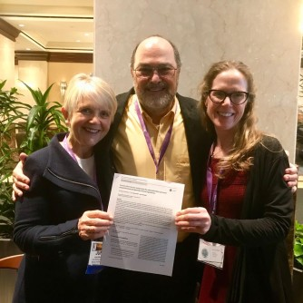 photo of June, Tim and Jenni holding research paper